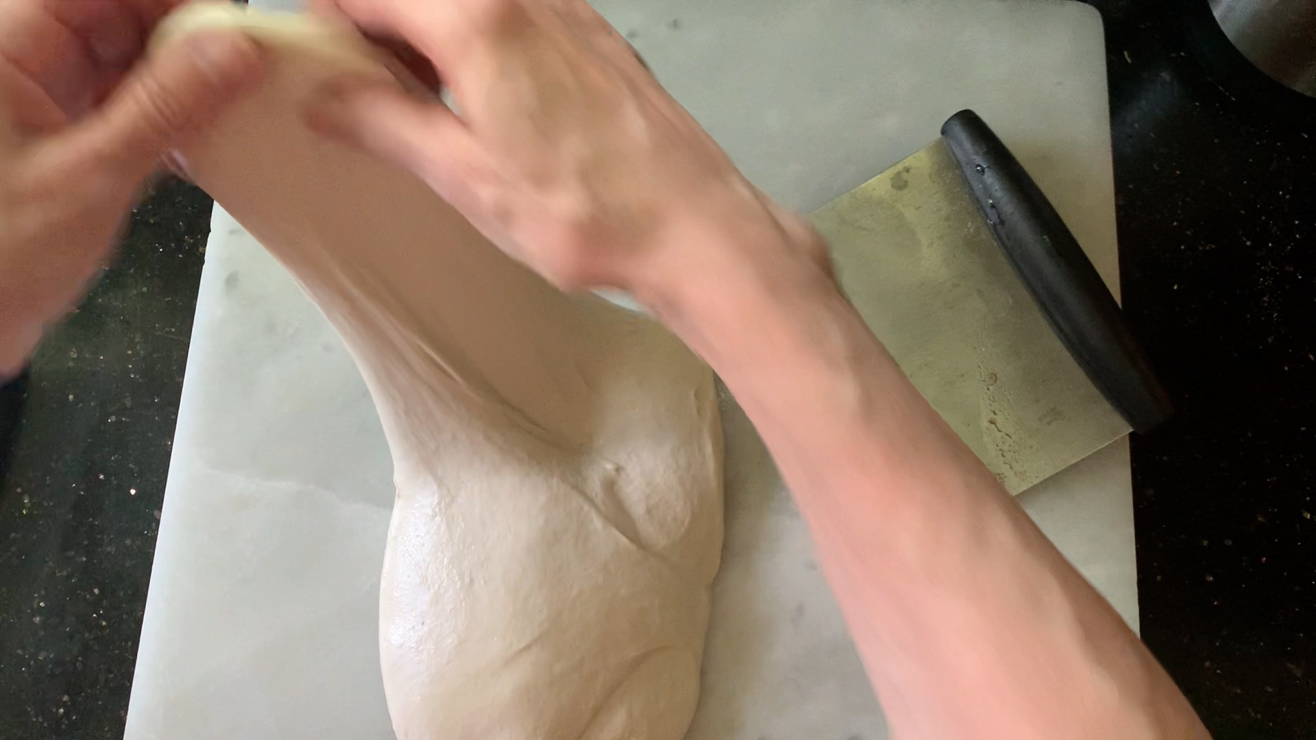 Stretching and folding the dough during pre-shape.