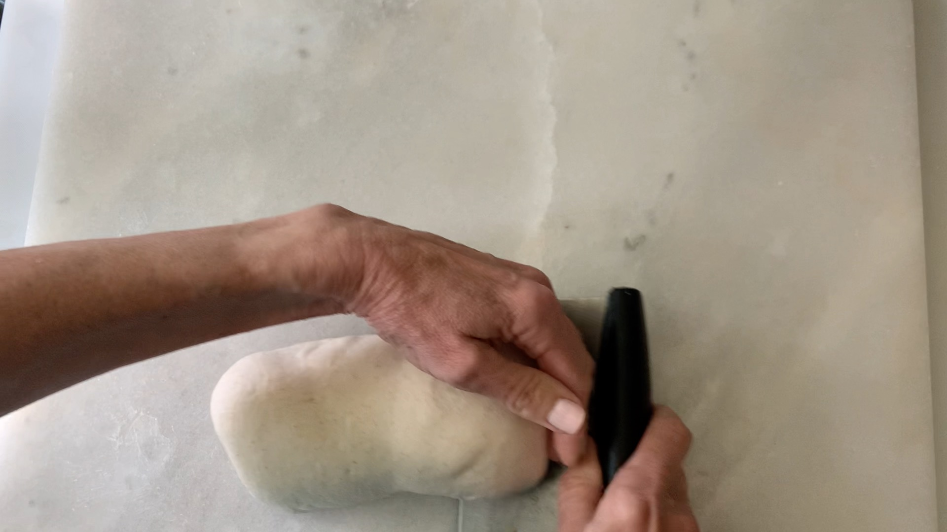 using hands and a bench scraper to make the dough more compact