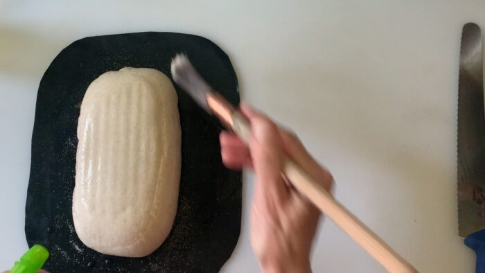 brushing and spraying the loaf with water--hoping for blisters