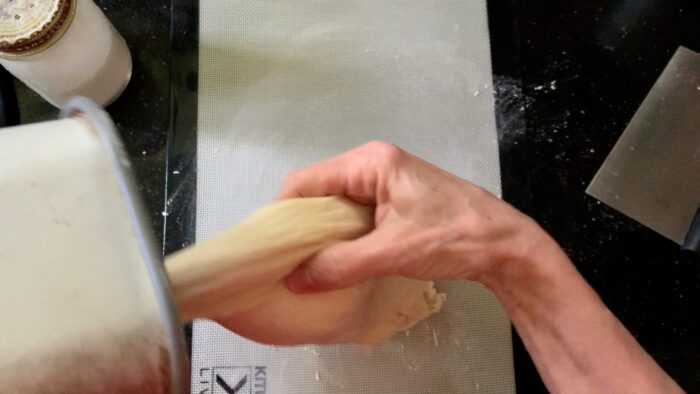 Pulling the dough out of the pan onto a floury surface.