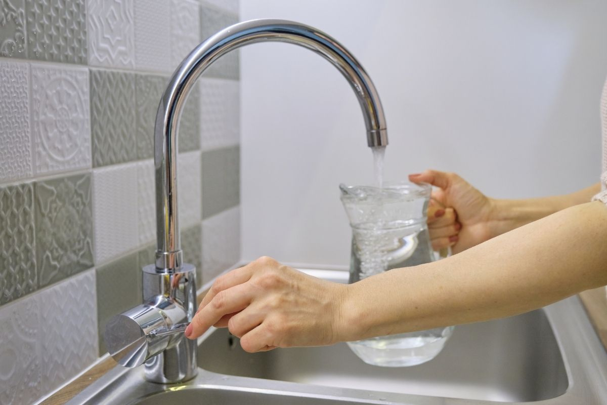 woman filling a pitcher with tap water