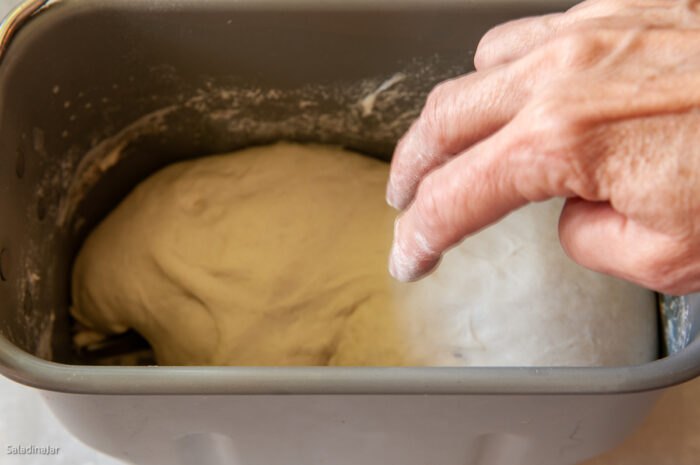 testing dough with two floury fingers