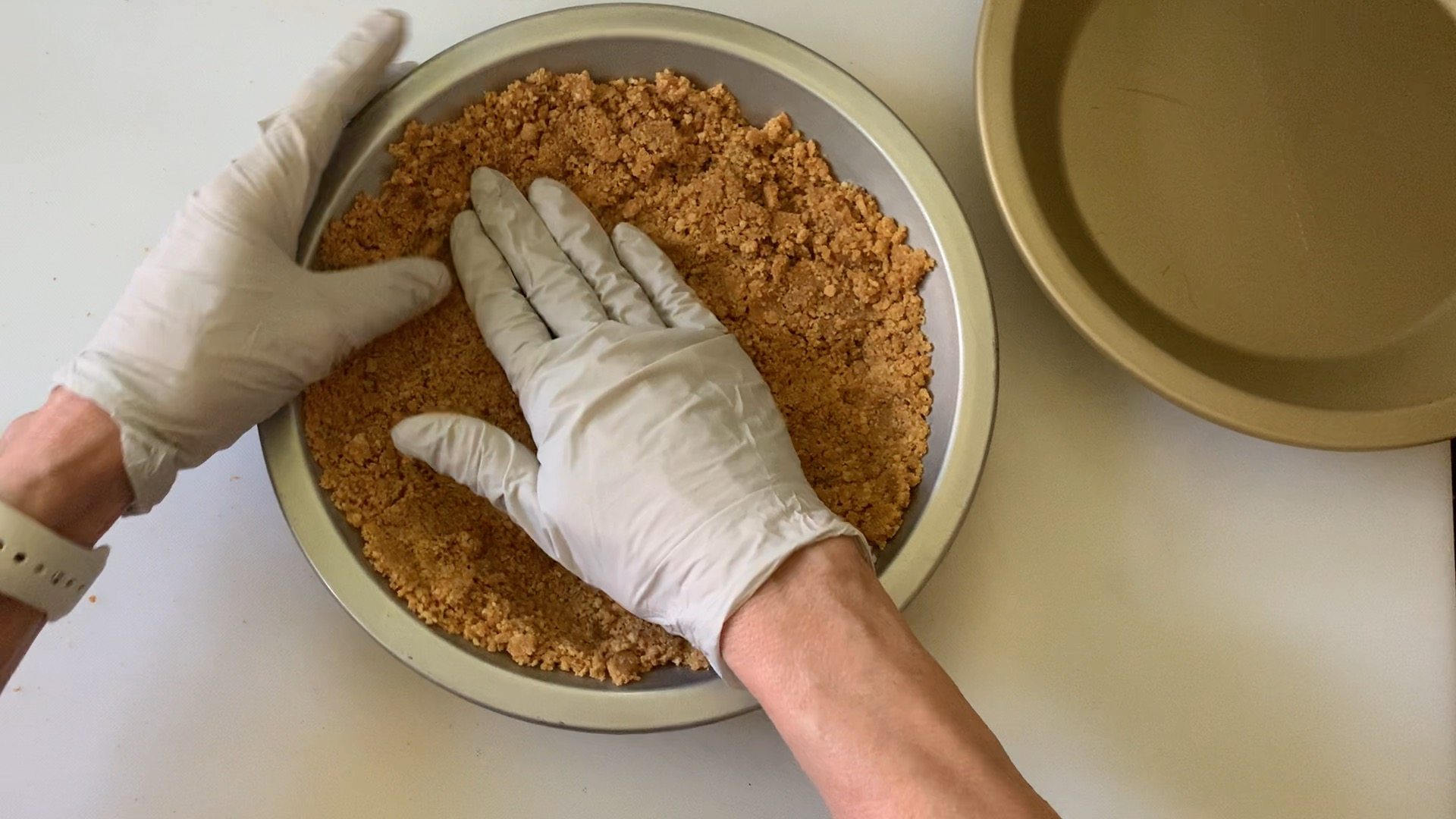 Using gloved hands to pat down crumbs