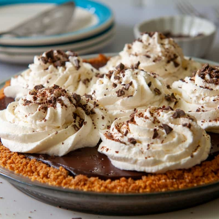 uncut microwave chocolate cream pie with a graham cracker crust and whipped cream topping